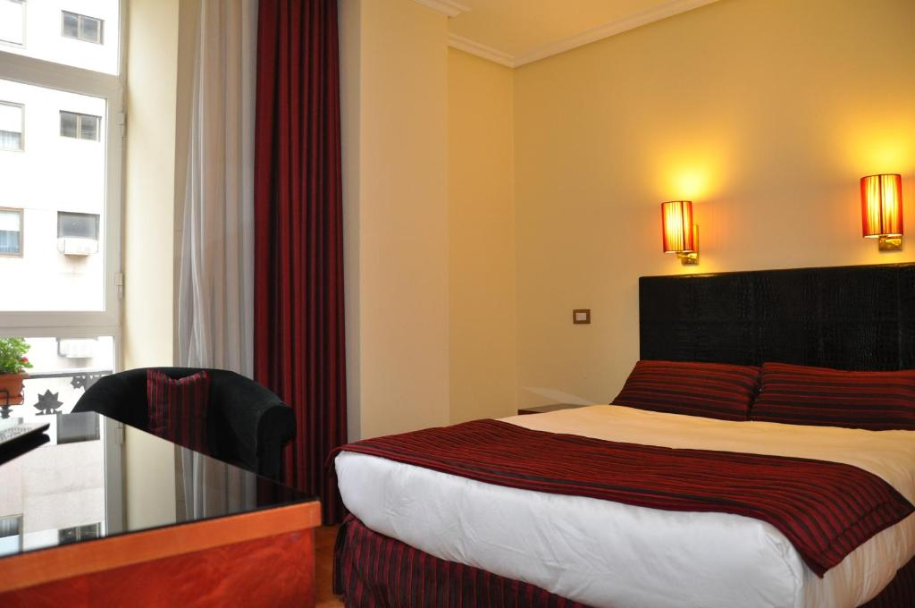 A bed or beds in a room at Hotel Compostela Vigo