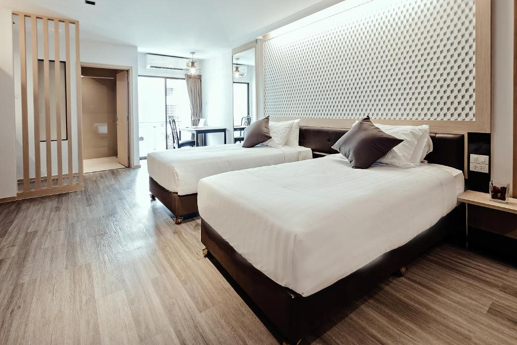 A bed or beds in a room at Three Sukhumvit Hotel