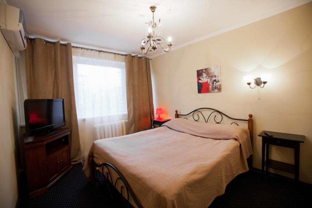 A bed or beds in a room at Zvezda Zhiguley Hotel