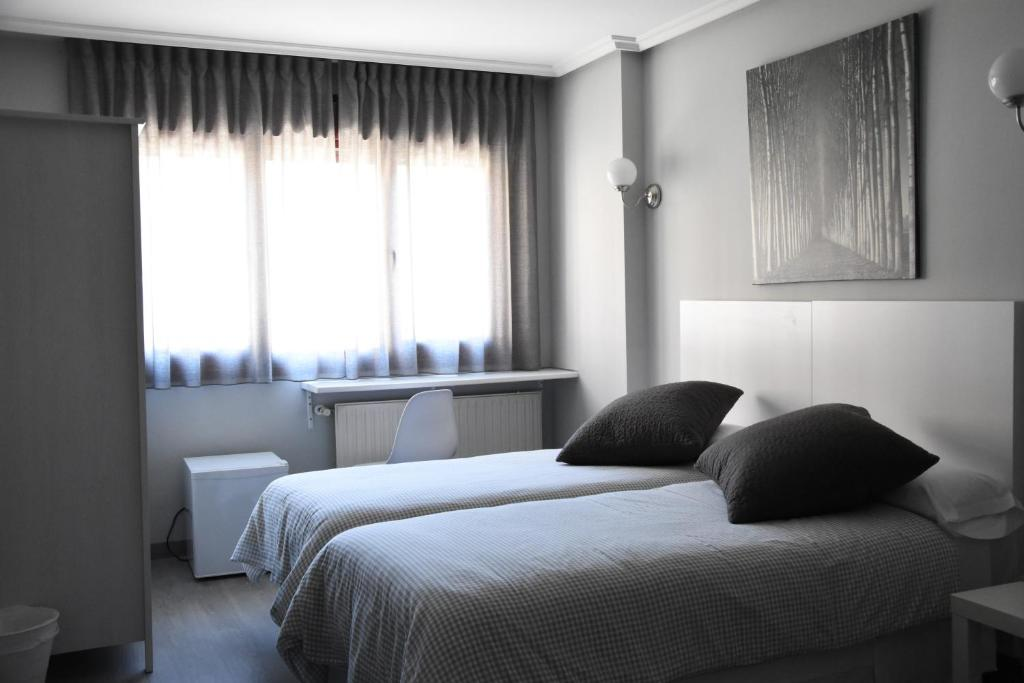 A bed or beds in a room at Hotel Carbayon