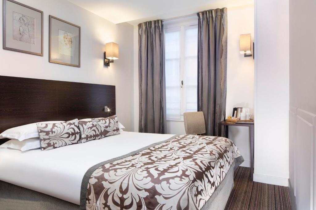 Een bed of bedden in een kamer bij Hôtel Paris Louvre Opéra