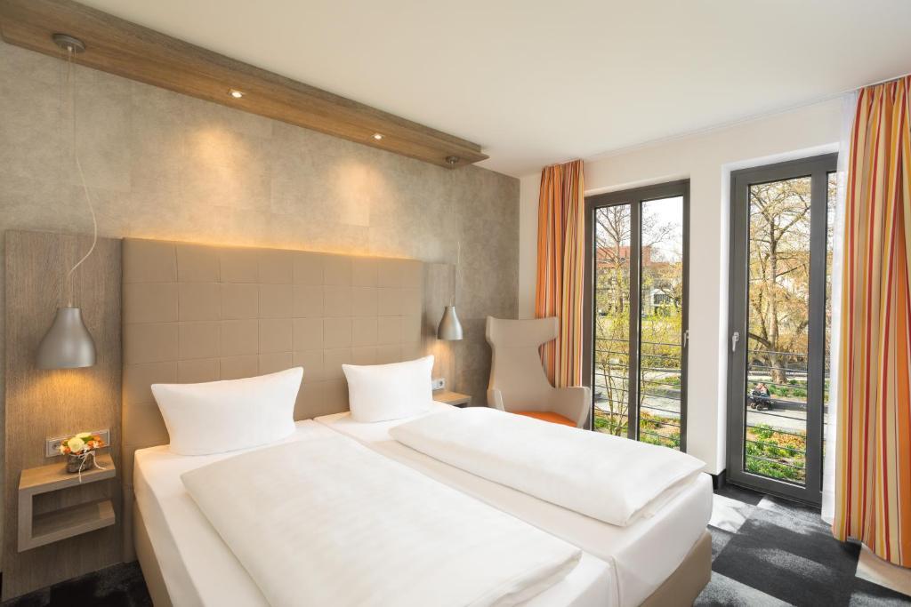 A bed or beds in a room at Hotel Krämerbrücke Erfurt
