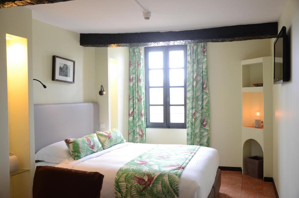 A bed or beds in a room at Hôtel Grimaldi