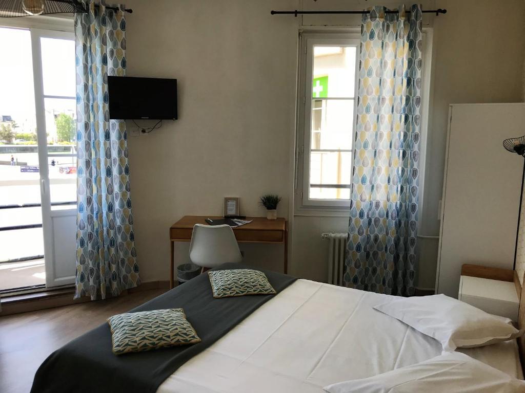 A bed or beds in a room at Hôtel L'Estran