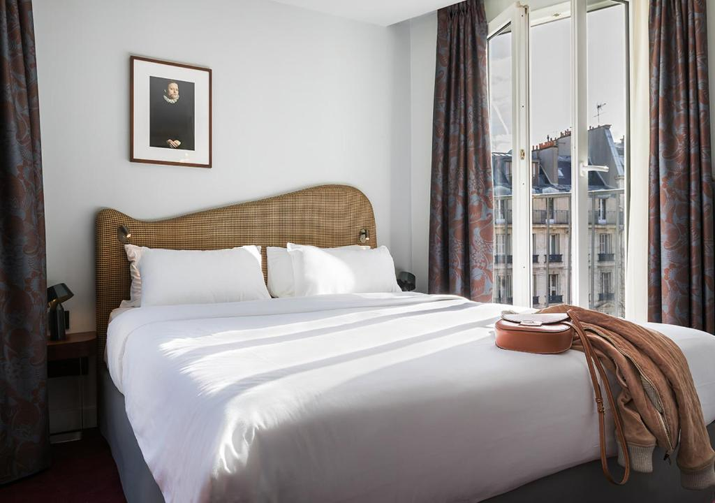 A bed or beds in a room at Hôtel Belloy Saint Germain