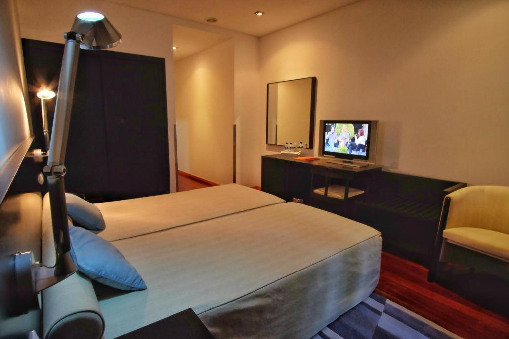 A bed or beds in a room at Hotel Vila Luena