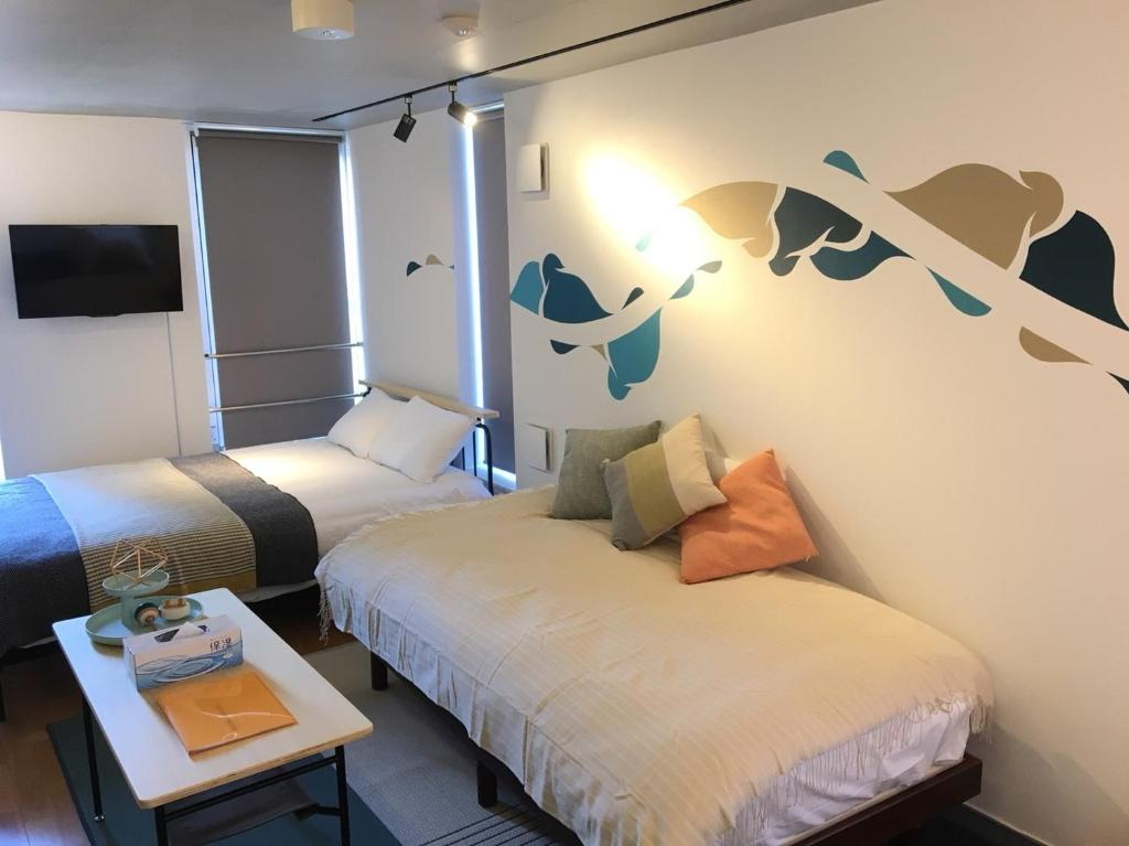 A bed or beds in a room at Art Apartment AOCA Sanno MHAK