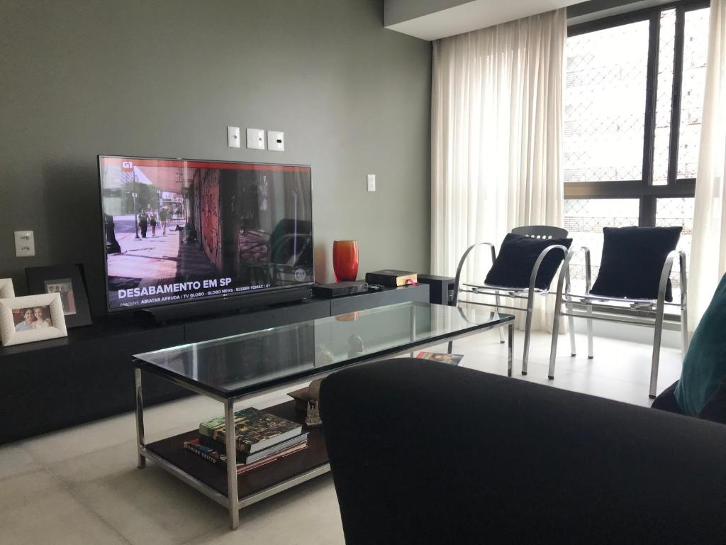 A television and/or entertainment center at Apto Luxo Boa Viagem LocDay
