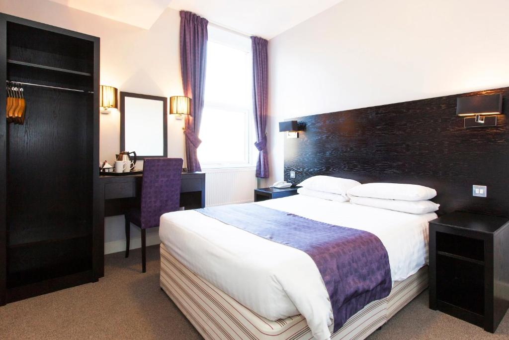 A bed or beds in a room at The Abbey Lodge Hotel