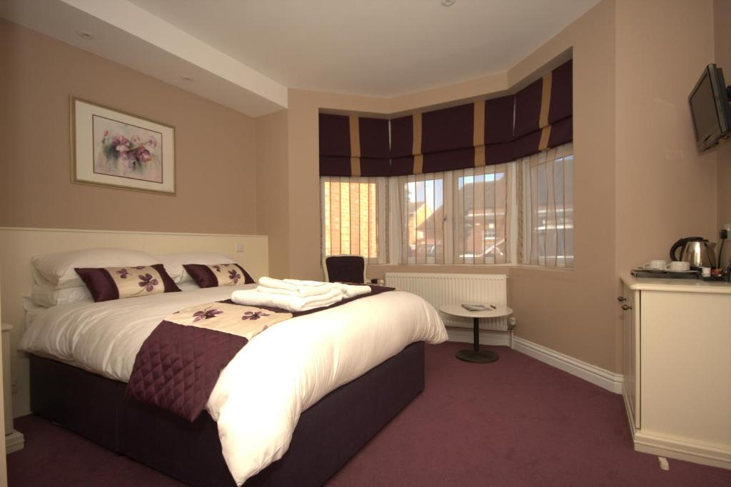 A bed or beds in a room at Highclere Hotel
