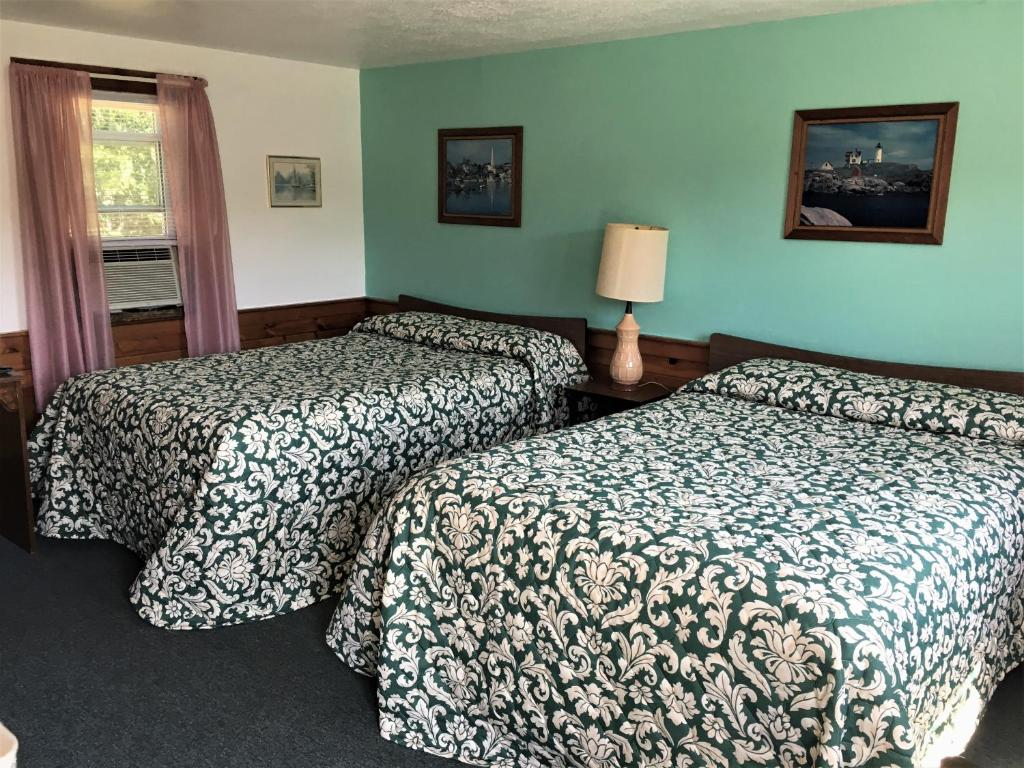 A bed or beds in a room at Bass River Motel
