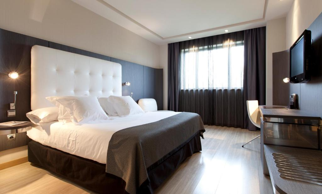 A bed or beds in a room at Hotel Maydrit Airport