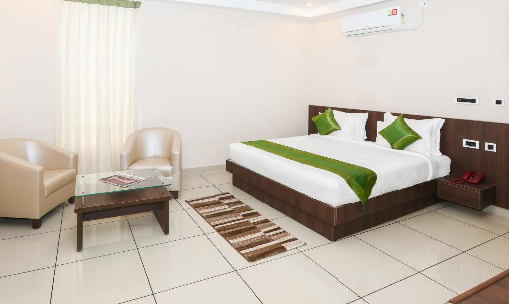 A bed or beds in a room at Treebo Trend Durga Bhoji Grand,Coorg