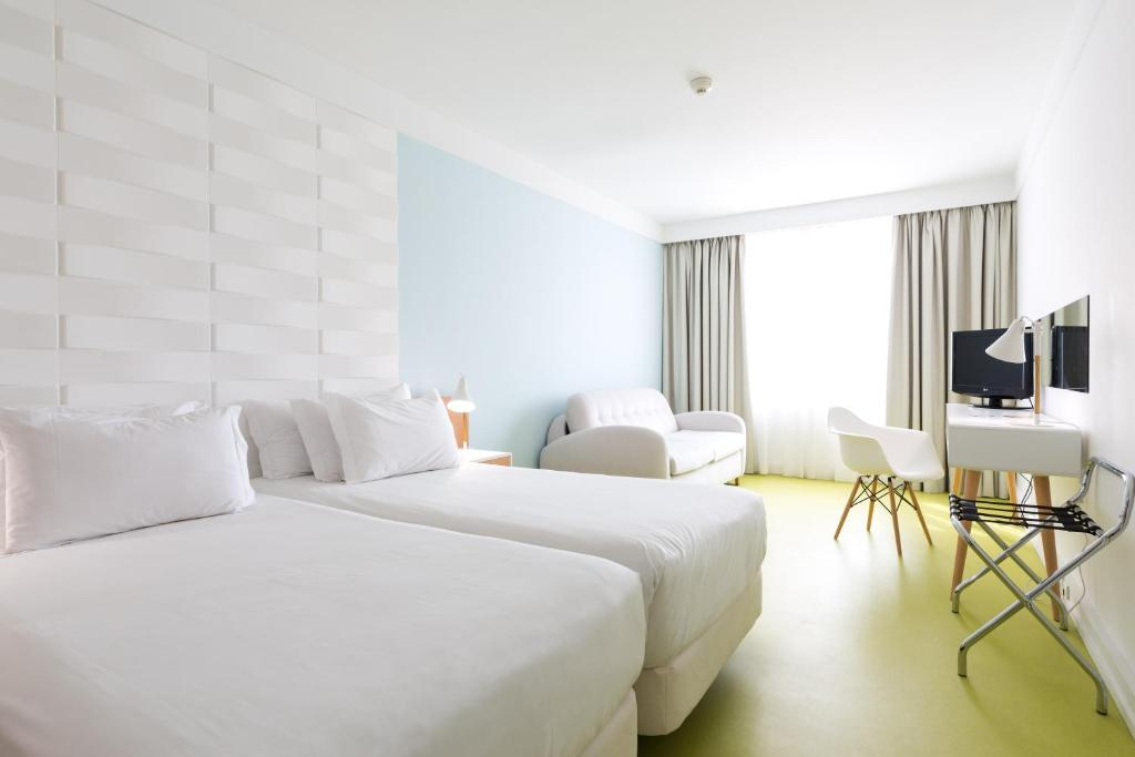 A bed or beds in a room at Legendary Porto Hotel
