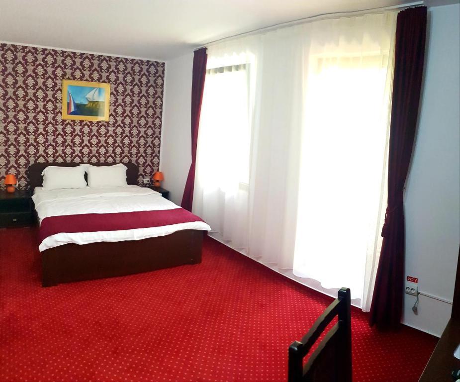 Un pat sau paturi într-o cameră la Hotel Hermes
