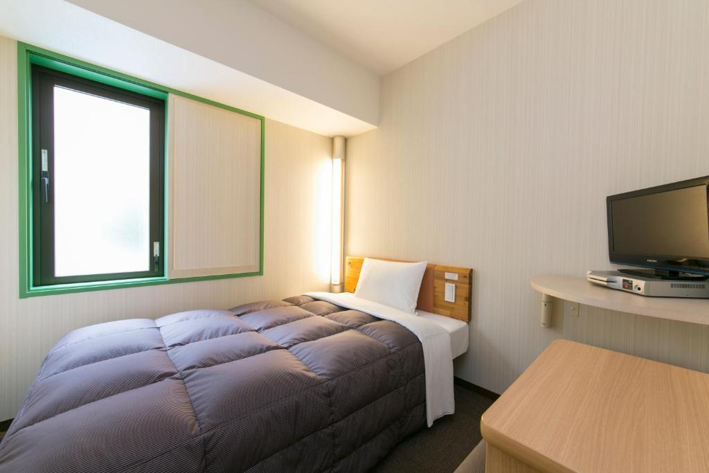 A bed or beds in a room at R&B Hotel Umeda East