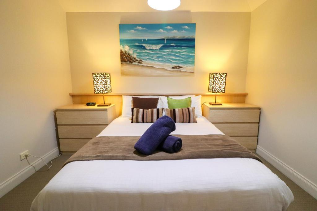 A bed or beds in a room at Ironbark Family Townhouse at Raffertys Resort