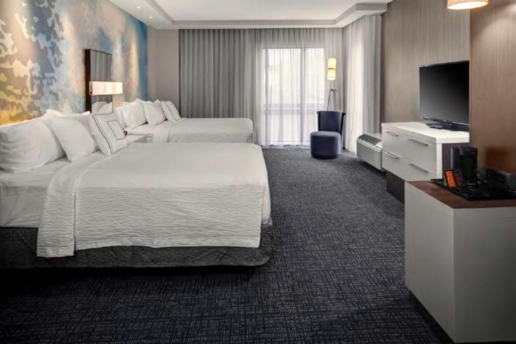 A bed or beds in a room at Courtyard by Marriott Carrollton