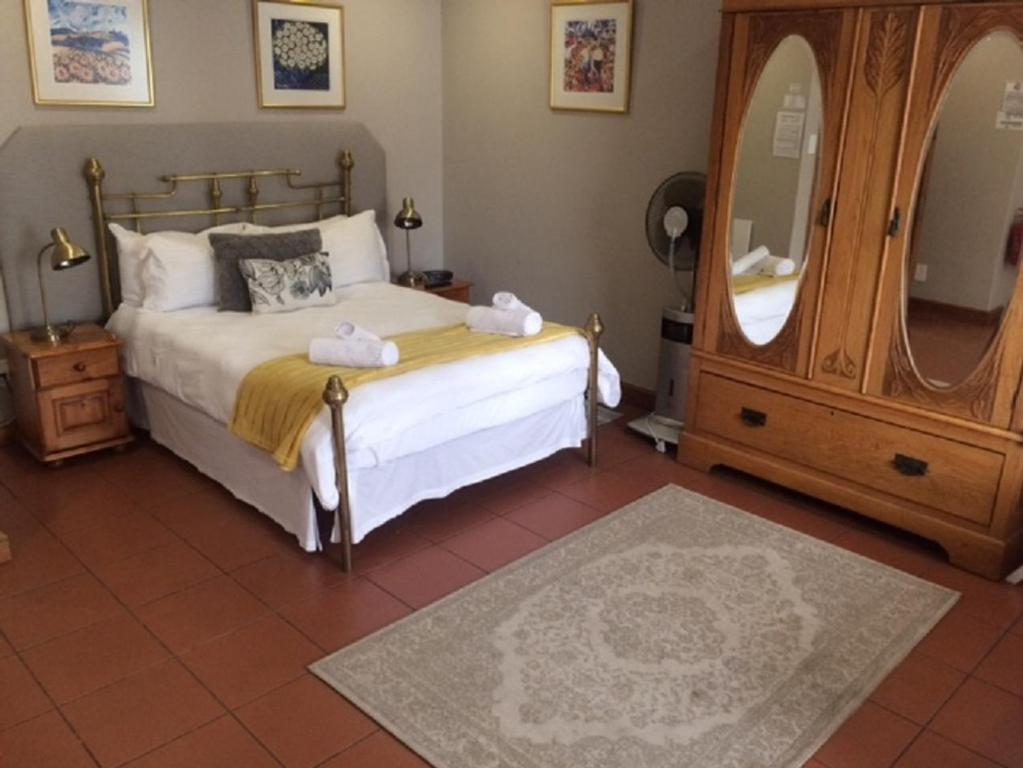 A bed or beds in a room at De Waterkant Lodge