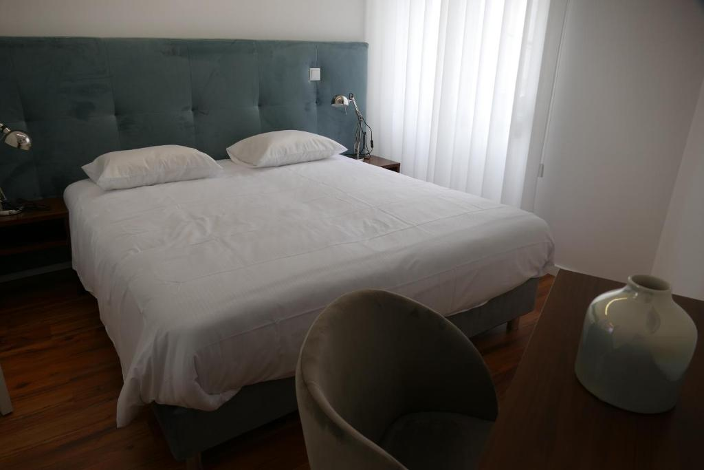 A bed or beds in a room at Guest House Eça - Centro Histórico Leiria