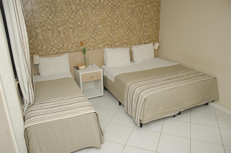 A bed or beds in a room at Serra Plaza Hotel