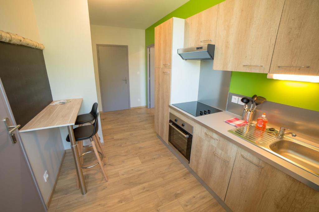 A kitchen or kitchenette at Appart Hotel de la Souleuvre