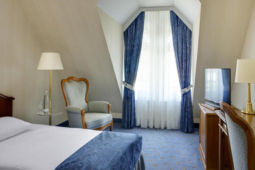 A bed or beds in a room at Dorint Parkhotel Meißen