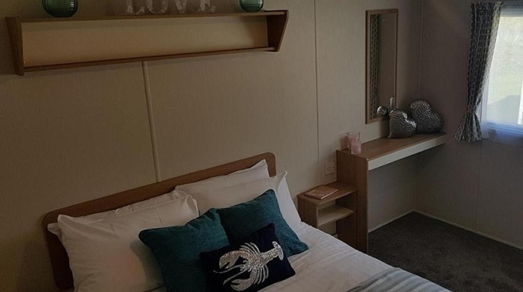 A bed or beds in a room at Caravan at Park Leisure - Pentire
