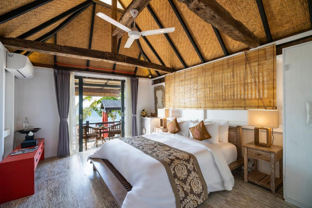A bed or beds in a room at Amed Lodge by Sudamala Resorts