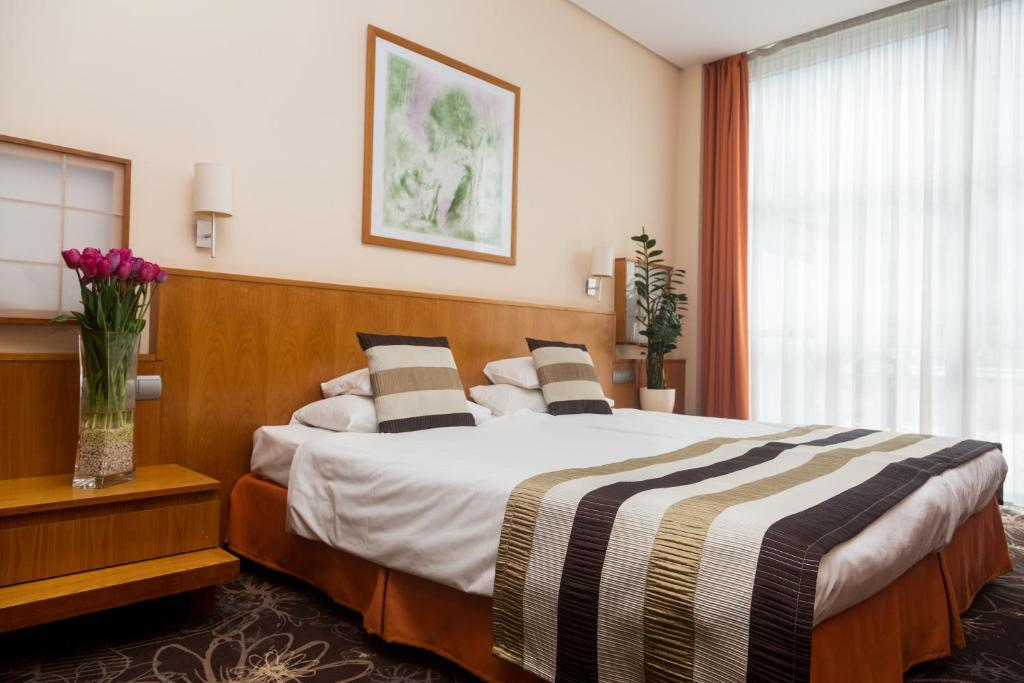 A bed or beds in a room at Hotel Lycium Debrecen