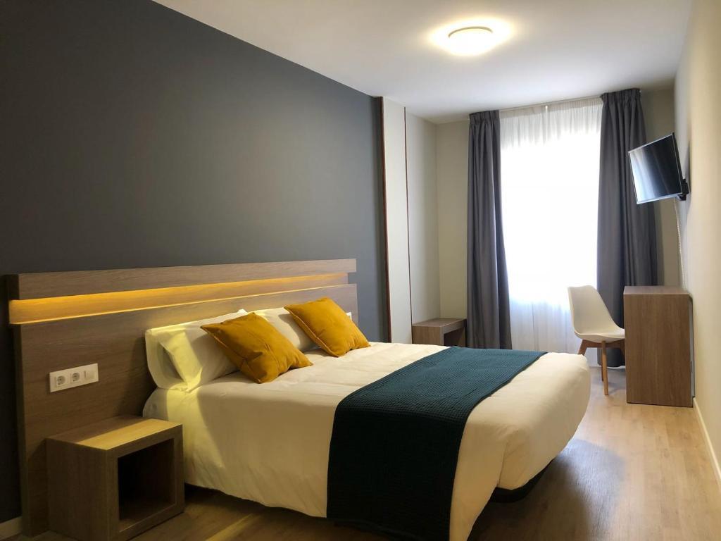 A bed or beds in a room at Hotel Alda Estación Pontevedra