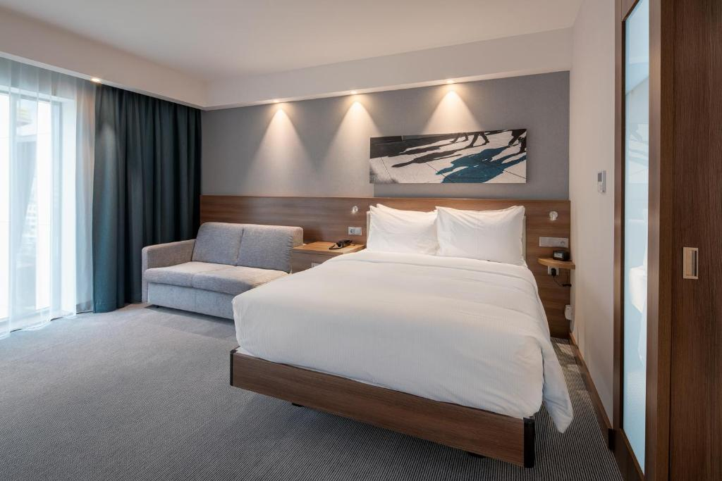 A bed or beds in a room at Hampton By Hilton Warsaw Mokotow