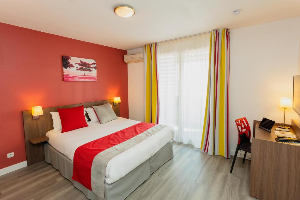 A bed or beds in a room at Appart-Hôtel Mer & Golf City Perpignan Centre