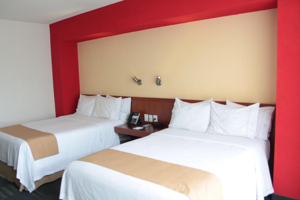A bed or beds in a room at Holiday Inn Express Guadalajara Expo