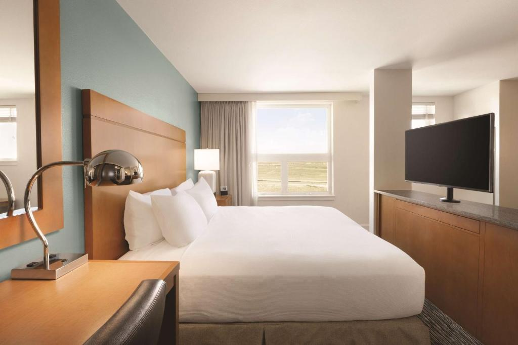 A bed or beds in a room at Hyatt House Denver Airport
