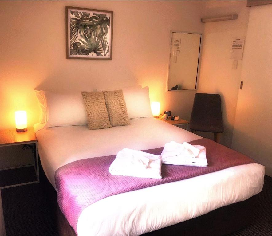 A bed or beds in a room at Aabon Apartments & Motel