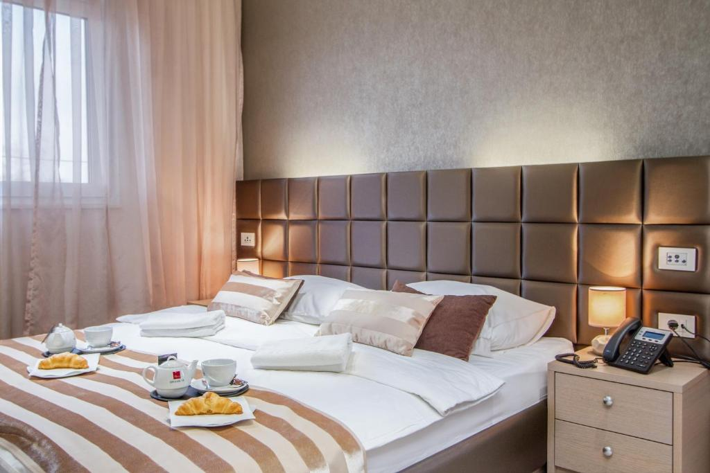 A bed or beds in a room at Royal Airport Hotel