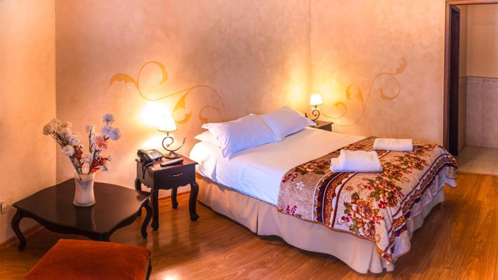 A bed or beds in a room at Villa de Tacvnga Hotel