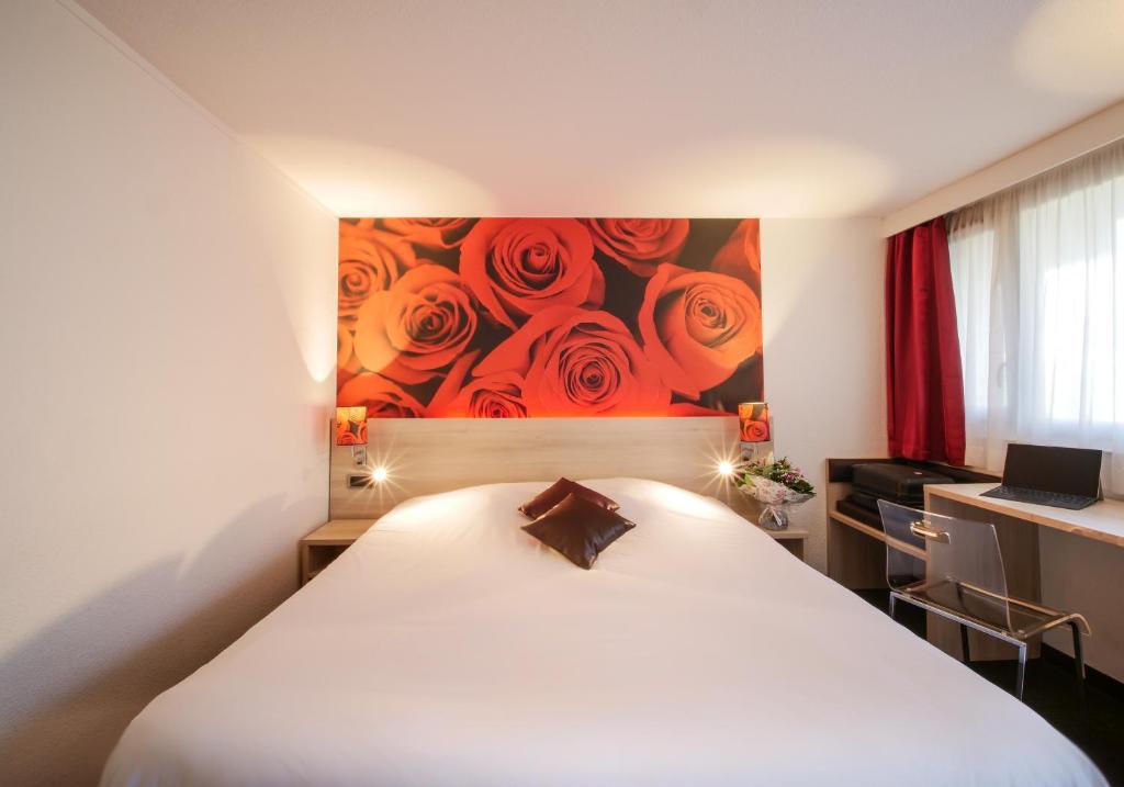 A bed or beds in a room at Hôtel Inn Design Resto Novo Sablé