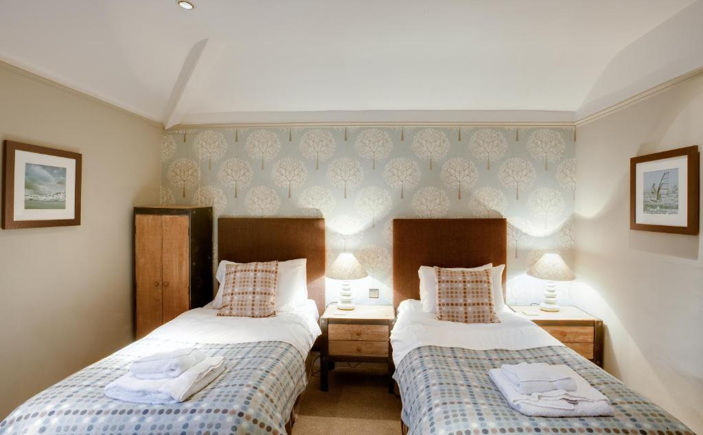 A bed or beds in a room at Anglesey Arms Hotel