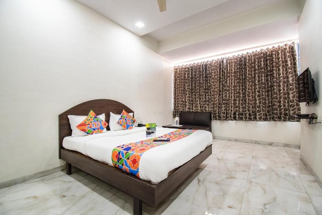A bed or beds in a room at FabHotel Sahara Inn Nashik
