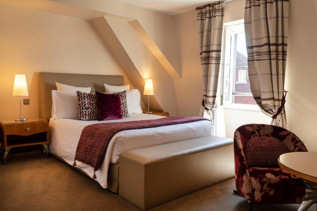 A bed or beds in a room at Hotel & Spa REGENT PETITE FRANCE