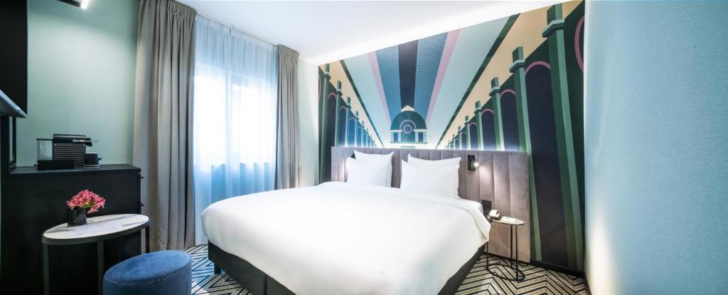 A bed or beds in a room at Hotel Hubert Grand Place
