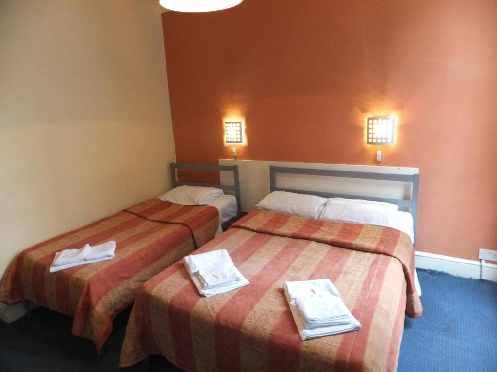 A bed or beds in a room at Gresham Hotel Bloomsbury