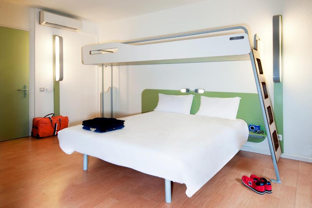 A bed or beds in a room at Hotel Inn Design Issoudun