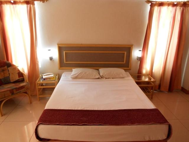 A bed or beds in a room at Elixir Hotel And Serviced Apartments