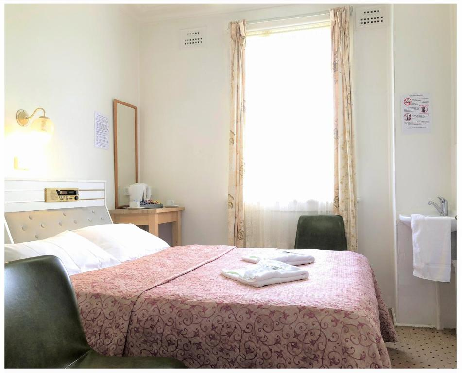 A bed or beds in a room at Clarendon Budget