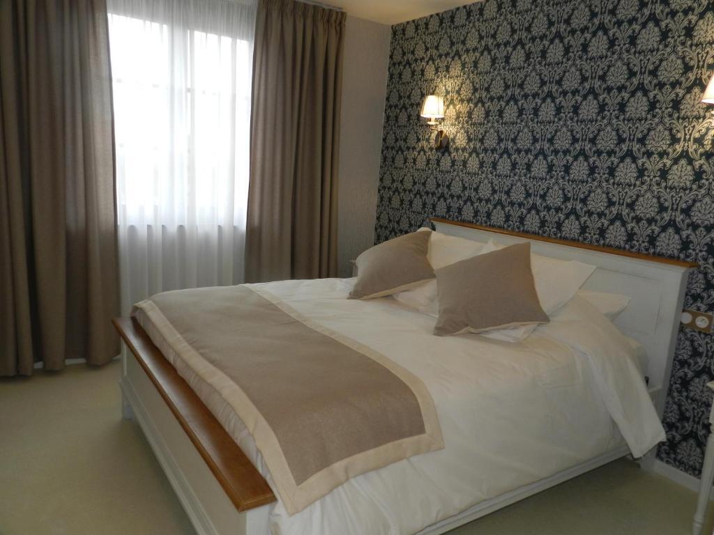 Un ou plusieurs lits dans un hébergement de l'établissement Hôtel - Spa - Restaurant LA VENISE VERTE