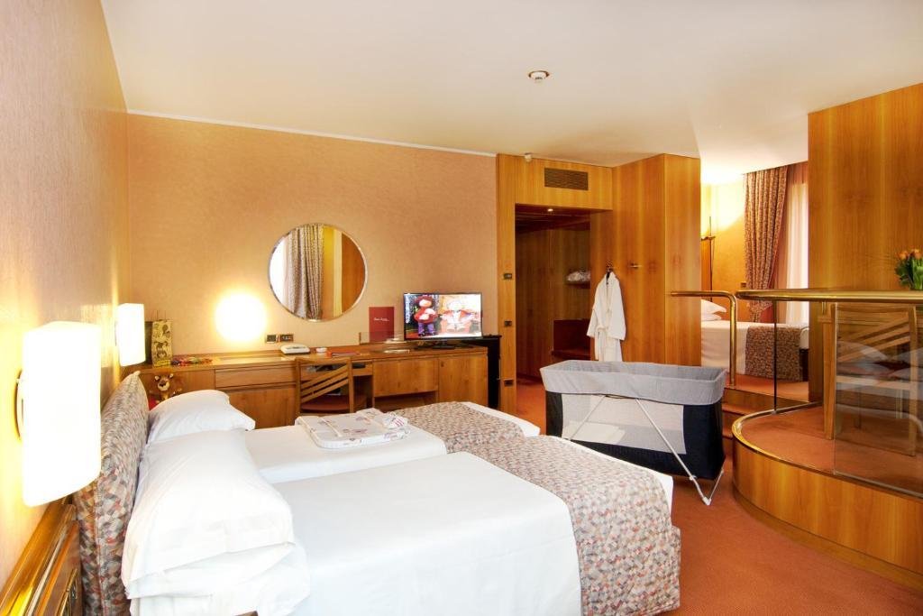 Un ou plusieurs lits dans un hébergement de l'établissement Hotel Michelangelo