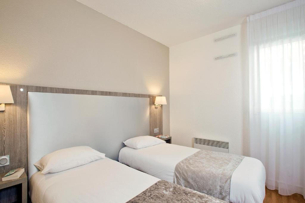 Кровать или кровати в номере Séjours & Affaires Reims Clairmarais